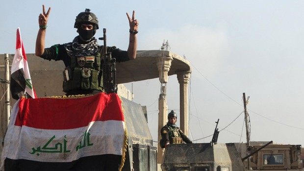 A member of the Iraqi security forces gestures at a government complex in the city of Ramadi, December 28, 2015.