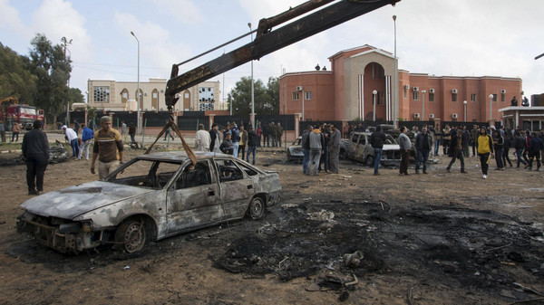 The burnt-out remains of a car is removed from a road at the site of a bomb blast in Shahat, eastern Libya, November 9, 2014.