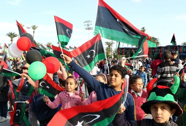 Libyans wave their national flags during a rally to celebrate the country's 64th independence anniversary at the Martyrs square in the capital Tripoli, on December 24, 2015. AFP PHOTO / MAHMUD TURKIA / AFP / MAHMUD TURKIA
