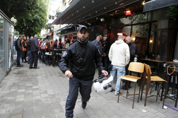 A policeman runs at the scene of a shooting incident in Tel Aviv, Friday. NIR ELIAS / Reuters