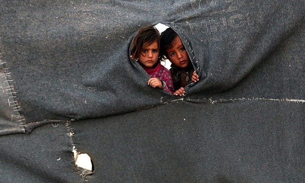 Two Syrian child refugees peer through a makeshift barrier at the Zaatari camp in Jordan. Photograph: Mohammad Abu Ghosh/Xinhua Press/Corbis