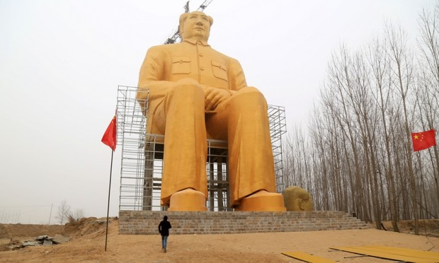 A visitor shows the scale of the huge statue. Photograph: Imaginechina/Rex/Shutterstock