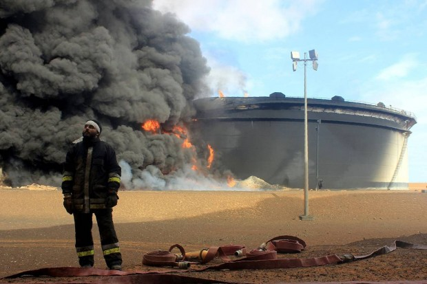 A firefighter stands in front of an oil storage tank in northern Libya's Ras Lanouf region on Jan. 23 after attacks launched by Islamic State. Libya is emerging as a new destination of choice for extremists, a report released by a security consulting firm said Wednesday. PHOTO: AGENCE FRANCE-PRESSE/GETTY IMAGES