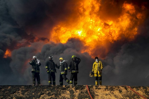 Firefighters trying to put out a fire in an oil tank in the port of Es Sider, Libya, on Jan. 6. The fires were extinguished over the weekend and now officials are trying to sell oil stored at the neighboring port of Ras Lanuf abroad. PHOTO: REUTERS