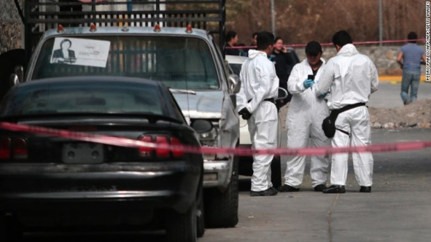 Forensic investigators gather outside residence of slain mayor