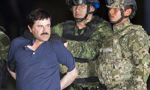 Joaquin 'El Chapo' Guzman is publicly escorted to a helicopter in handcuffs by Mexican soldiers and marines at a federal hangar in Mexico City on Friday. Photograph: Eduardo Verdugo/AP