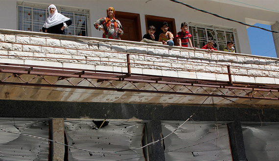 People look out from a balcony above shops with damaged shutter fronts in the Madaya area, near Damascus, May 6, 2012.  (photo by REUTERS/Khaled al-Hariri)