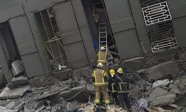 Rescue personnel work at a damaged building. Photograph: Pichi Chuang/Reuters