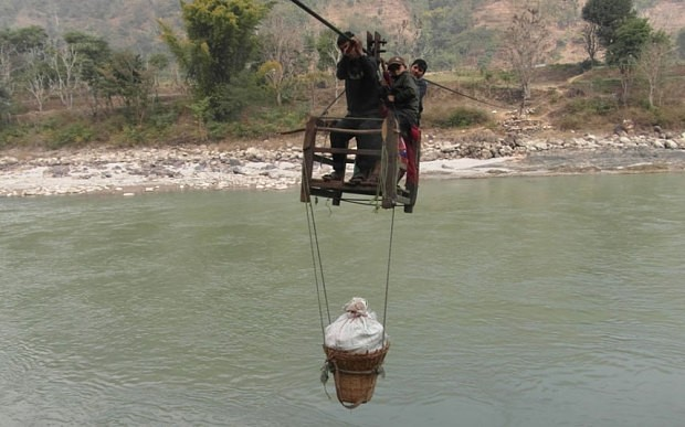 Residents of Dhaing village use a wooden trolley suspended via a cable to cross Trishuli River  Photo: Manish Duwadi / Barcroft India