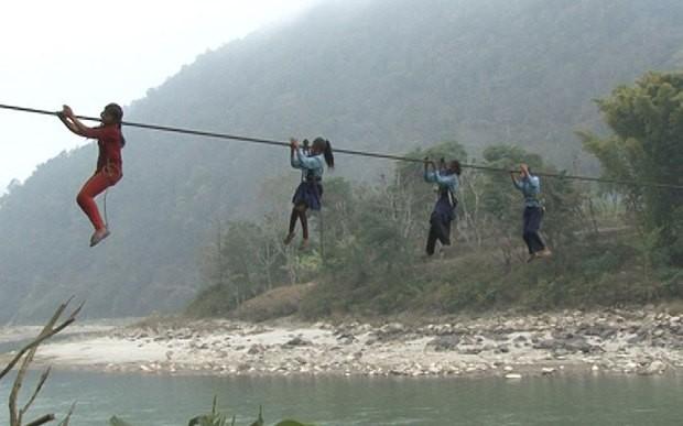 Schoolgirls cross Trishuli River via a rope-bridge each day  Photo: Manish Duwadi / Barcroft India