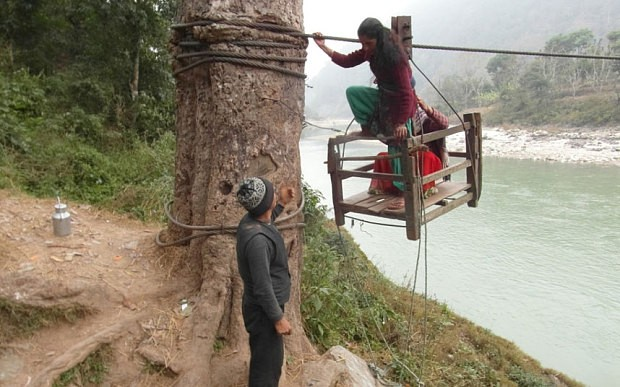 A girl being helped by a local after she crossed Trishuli River using a rope-bridge  Photo: Manish Duwadi / Barcroft India