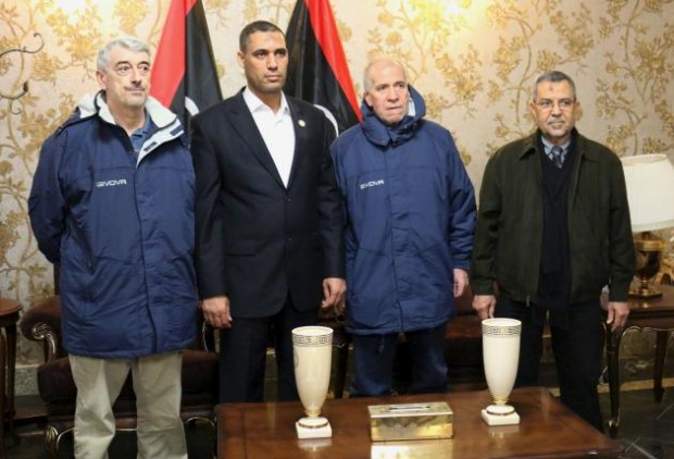 Tripoli-based Libyan Foreign Minister Ali Abu Zakouk (R) stands with Gino Pollicardo (L) and Filippo Calcagno (2nd R), two Italian civilians held hostage near the western Libyan city of Sabratha since last July, after they were freed, at Mitiga International Airport in Tripoli, Libya March 6, 2016. REUTERS/Hani Amara