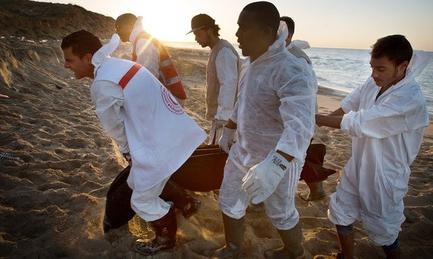Libyan Red Crescent workers recover a lifeless body of a drowned migrant on the beach in the eastern city of Tripoli, Libya. Photograph: Mohame Ben Khalifa/AP