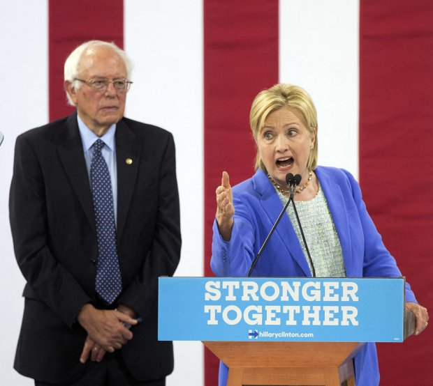 Sen. Bernie Sanders, I-Vt., listens as Democratic presidential candidate Hillary Clinton speaks during a rally in Portsmouth, N.H., Tuesday, July 12, 2016, where Sanders endorsed Clinton for president. (AP Photo/Jim Cole)