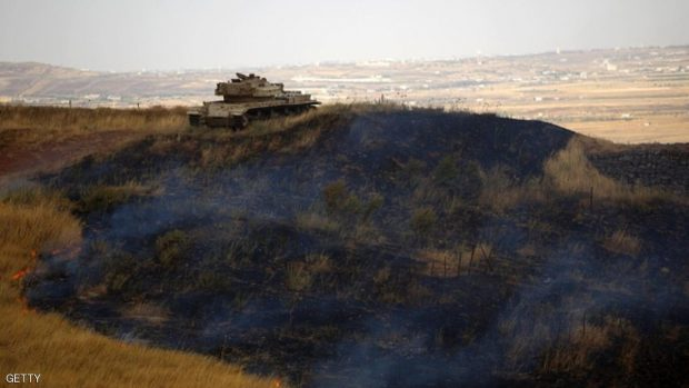 An disused Israeli tank is stationed on a burning mountain side in the El-Rom settlement in the Israeli-annexed Golan Heights on June 28, 2015, after it was hit by a rocket fired from the Syrian side. AFP PHOTO / JALAA MAREY        (Photo credit should read JALAA MAREY/AFP/Getty Images)