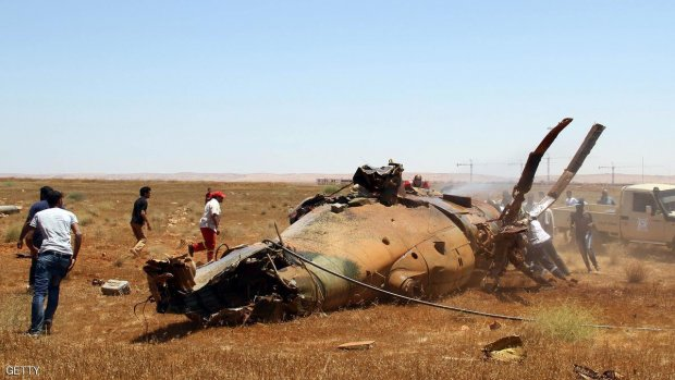 Libyan emergency personnel inspect the wreckage of a military helicopter that crashed during an airshow in the eastern city of Benghazi on July 4, 2013, killing two crew members and wounding a third, an airforce official told AFP. The accident occurred while a military parade was underway at the Benina airbase in Benghazi, Libya's second city and cradle of the 2011 uprising that toppled dictator Moamer Kadhafi. AFP PHOTO/ABDULLAH DOMA        (Photo credit should read ABDULLAH DOMA/AFP/Getty Images)