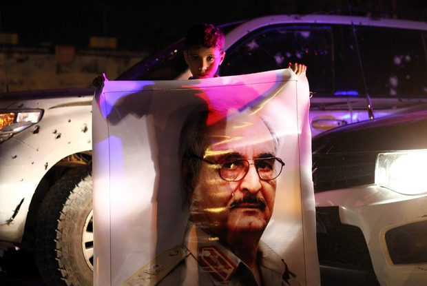A Libyan boy holds a portrait of Major-General Halifa Haftar as people celebrate the decision by their parliament to reject the UN proposals for a national unity government, in a public square in Benghazi late on October 19, 2015. A majority of lawmakers in Libya's internationally recognised parliament rejected a UN peace deal and a proposal for a national unity government, one of them said. AFP PHOTO / ABDULLAH DOMA / AFP PHOTO / ABDULLAH DOMA
