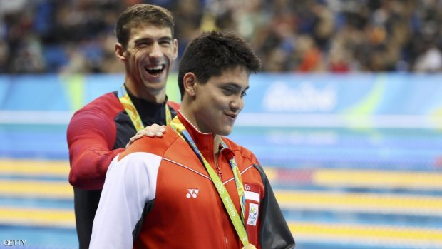 2016 Rio Olympics - Swimming - Victory Ceremony - Men's 100m Butterfly Victory Ceremony - Olympic Aquatics Stadium - Rio de Janeiro, Brazil - 12/08/2016. Joseph Schooling (SIN) of Singapore is congratulated by Michael Phelps (USA) of USA as they leave the podium.   REUTERS/Stefan Wermuth FOR EDITORIAL USE ONLY. NOT FOR SALE FOR MARKETING OR ADVERTISING CAMPAIGNS.