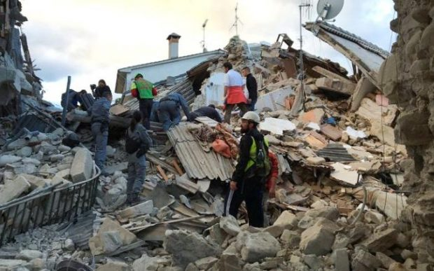 Rescuers at work at  a collapsed house following the quake in Amatrice