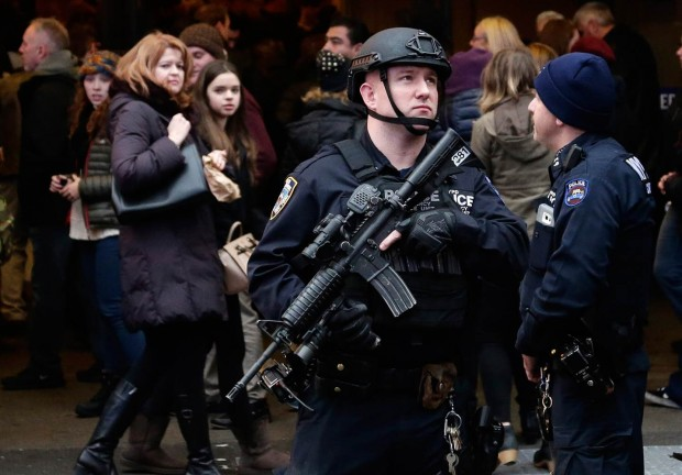 A member of the New York City Police department's Hercules team patrols in Times Square the day before New Year's Eve on Wednesday.  JASON SZENES / EPA