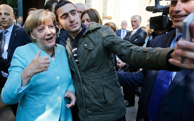 "German Chancellor Angela Merkel takes a ""selfie"" with an asylum-seeker."