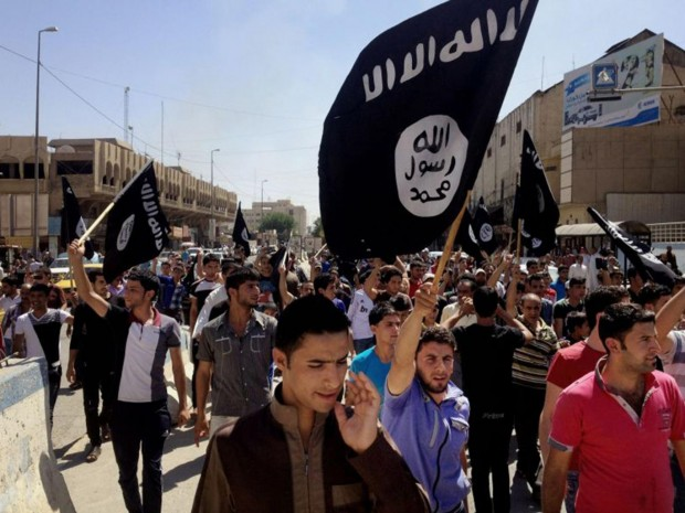 Crowds with Isis flags march past the provincial government offices in Mosul AP