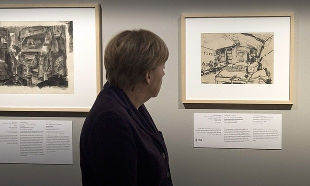 Chancellor Angela Merkel looks at an image from the Theresienstadt concentration camp during a preview of Art from the Holocaust in Berlin. Photograph: Handout/Bundesregierung via Getty Images