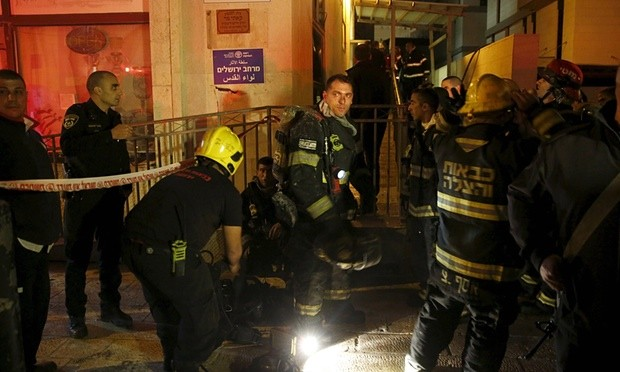 Israeli firefighters at the entrance to the building that houses the offices of human rights group B'Tselem. Photograph: Ronen Zvulun/Reuters