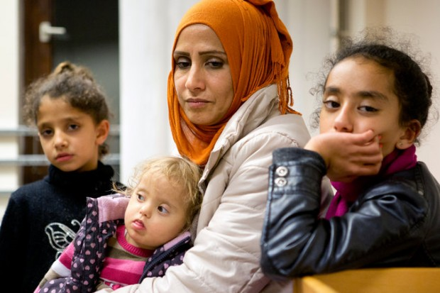 "A 35-year-old Syrian refugee, Samar, in November with her three daughters, then 2, 8 and 13, at a shelter in Berlin. ""Everybody knows there are two ways of paying the smugglers,"" she said. ""With money or with your body."" Samar refused a smuggler's advances in Turkey, and was threatened. Credit Djamila Grossman for The New York Times"