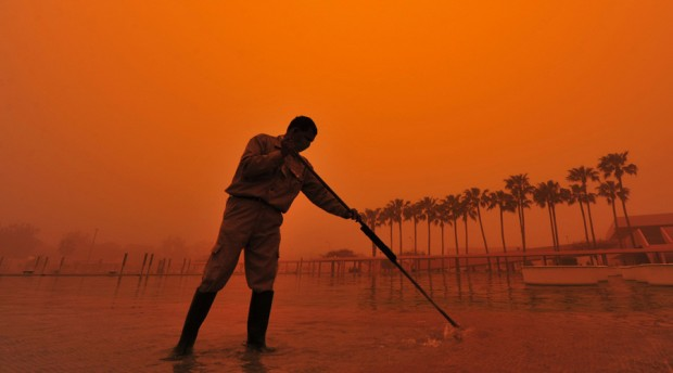 A worker cleans a fountain during a dust storm in Benghazi March 30, 2013. © Esam Al-Fetori / Reuters