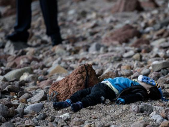 A man stands by the body of a refugee child washed up on a beach in Canakkale's Bademli district on January 30, 2016