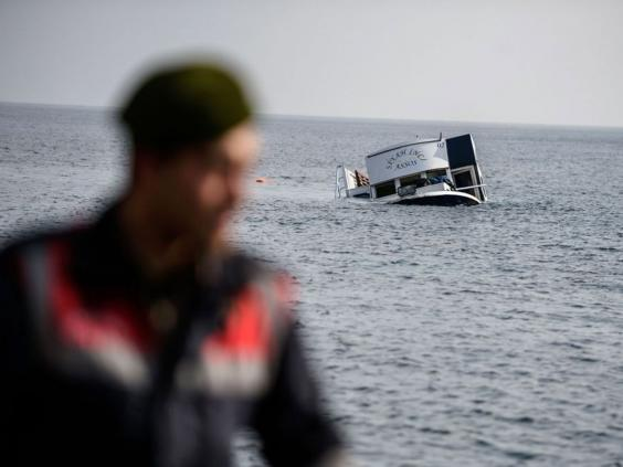 The sinking boat is seen behind a Turkish gendarme off the coast of Canakkale's Bademli district on January 30, 2016.