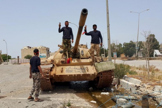 Members of the Libyan pro-government forces gesture as they stand on a tank in Benghazi, Libya, May 21, 2015. PHOTO: REUTERS