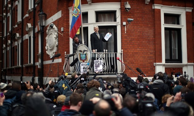 WikiLeak's founder, Julian Assange, holds up the UN panel's report as he addresses supporters and the media from the embassy balcony. Photograph: Carl Court/Getty