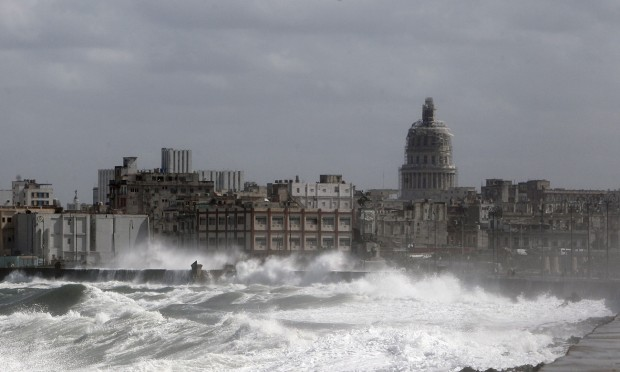 Waves break over Havana's seaside promenade. An end to the trade embargo may trigger a deluge of 10 million US tourists a year. Photograph: Ernesto Mastrascusa/EPA