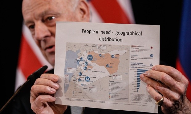 Staffan de Mistura, the UN secretary general's special envoy, holds up a map showing people in need in Syria. Photograph: Alexander Shcherbak/TASS