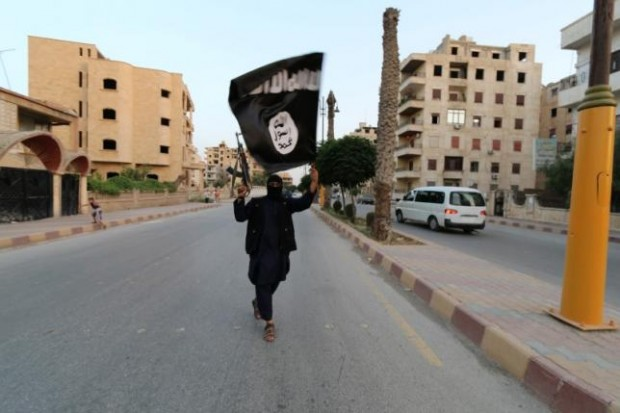 A member loyal to the Islamic State in Iraq and the Levant (ISIL) waves an ISIL flag in Raqqa June 29, 2014. REUTERS/STRINGER