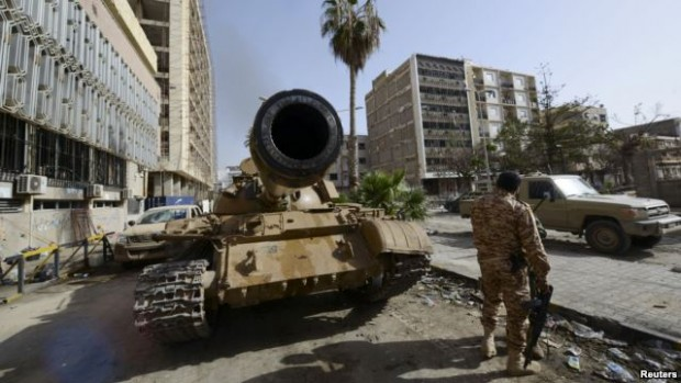 FILE - A member of the Libyan pro-government forces, backed by locals, stands near a tank in Benghazi, Libya. A majority of members (100 out of 196) of the internationally recognized parliament in Tobruk signed a statement Tuesday saying they agree with the latest in a string of plans to establish a unity government with rivals based in Tripoli.
