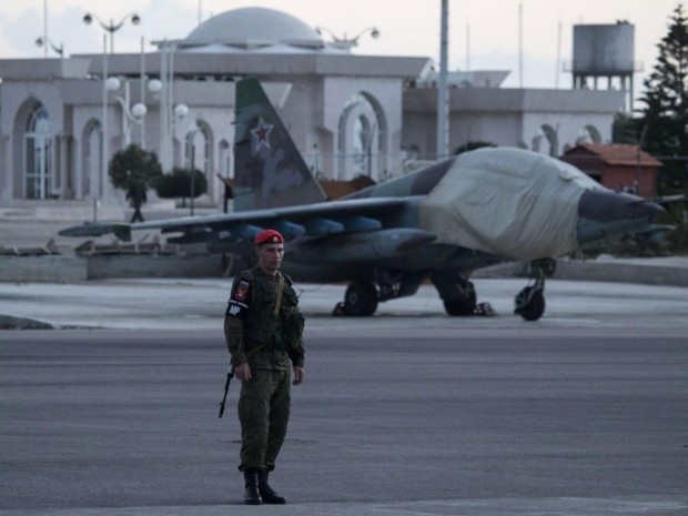 A Russian soldier guards a jet parked at Hemeimeem air base in Syria. Russian warplanes have mostly stayed on the ground since the cease-fire began AP