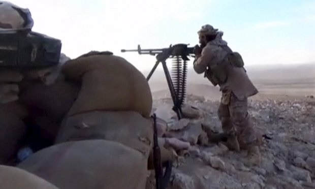An Isis fighter fires a machine gun in this still image taken from a video said to be taken on the outskirts of Palmyra and uploaded on 21 March. Photograph: Reuters