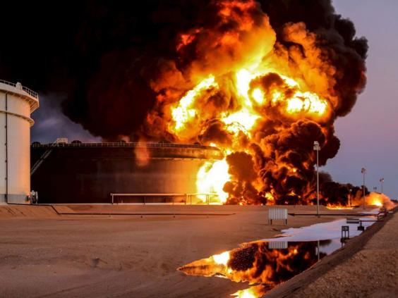 Fire rises from an oil tank in Ras Lanuf, Libya. Attacks against Libya's biggest oil terminals in recent weeks have been lethal and sustained