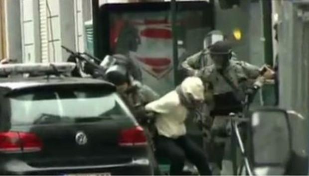 The moment Salah Abdeslam is bundled into a police car following his capture