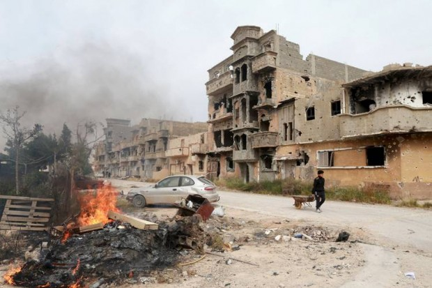 A man walking past destroyed buildings after clashes between military forces loyal to Libya's internationally recognized government and Islamist fighters in Benghazi on Sunday. PHOTO: ESAM OMRAN AL-FETORI/REUTERS