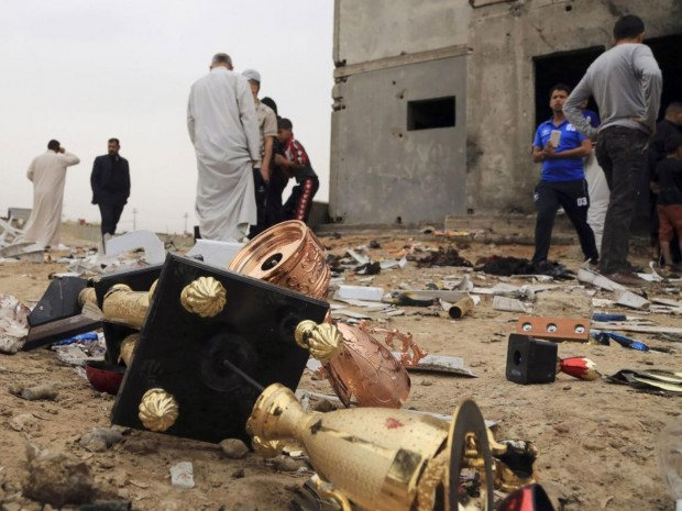 Broken trophies lie on the ground as people inspect the aftermath of a suicide bombing at a small football stadium in Iskandariya AP