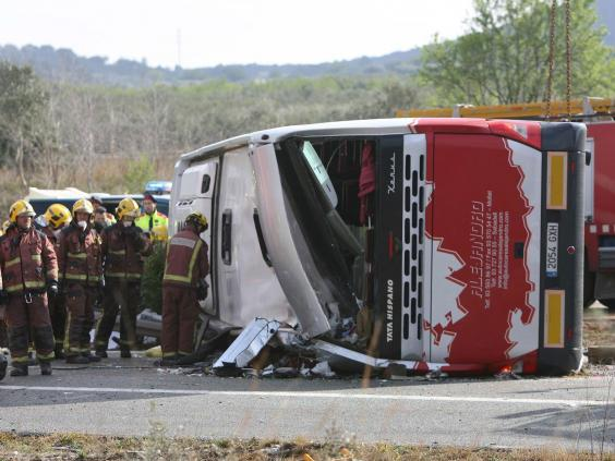 Firemen work at the site of a coach crash that has left at least 14 students dead at the AP-7 motorway in Freginals, in the province of Tarragona, northeastern Spain (EPA)