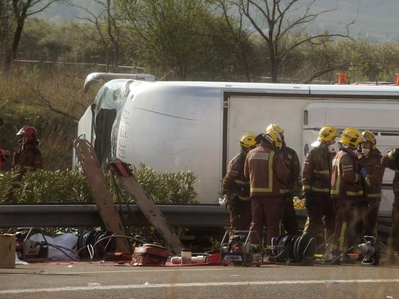Emergency services personnel stand at the scene of a bus accident (AP)