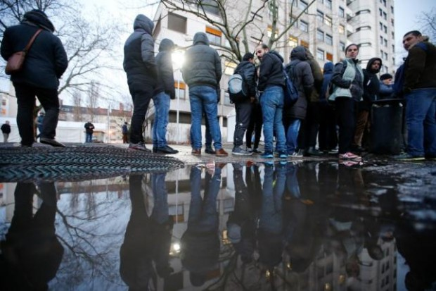Migrants are reflected in a puddle as they queue in front of the compound of the Berlin Office of Health and Social Affairs (LAGESO) for their registration process, early morning in Berlin, Germany, February 2, 2016. REUTERS/Fabrizio Bensch