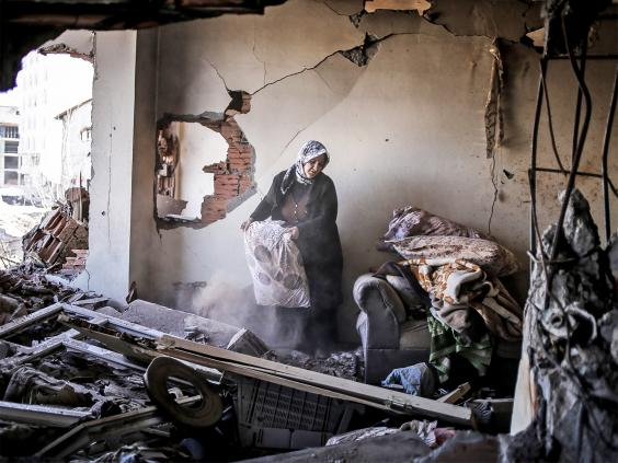 A woman inspects her belongings in her ruined home in Cizre. Turkish authorities have scaled down a 24-hour curfew imposed on the mainly Kurdish town