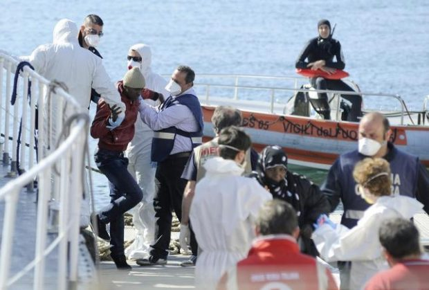 Migrants are helped as they disembark from a Coast Guard boat in the Sicilian harbour of Palermo