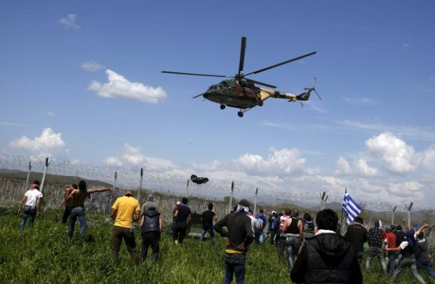 Migrants and refugees react as a Macedonian police helicopter flies over during clashes next to a border fence at a makeshift camp at the Greek-Macedonian border near the village of Idomeni, Greece, April 10, 2016. REUTERS/Stoyan Nenov